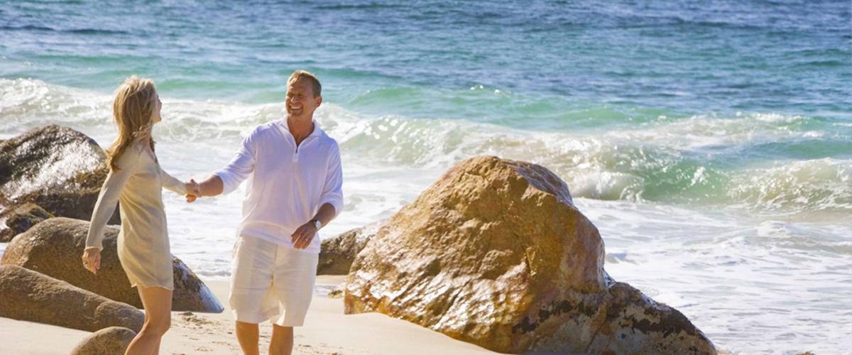 Relaxed couple walking on the beach at El Paredon villas in Puerto Vallarta.